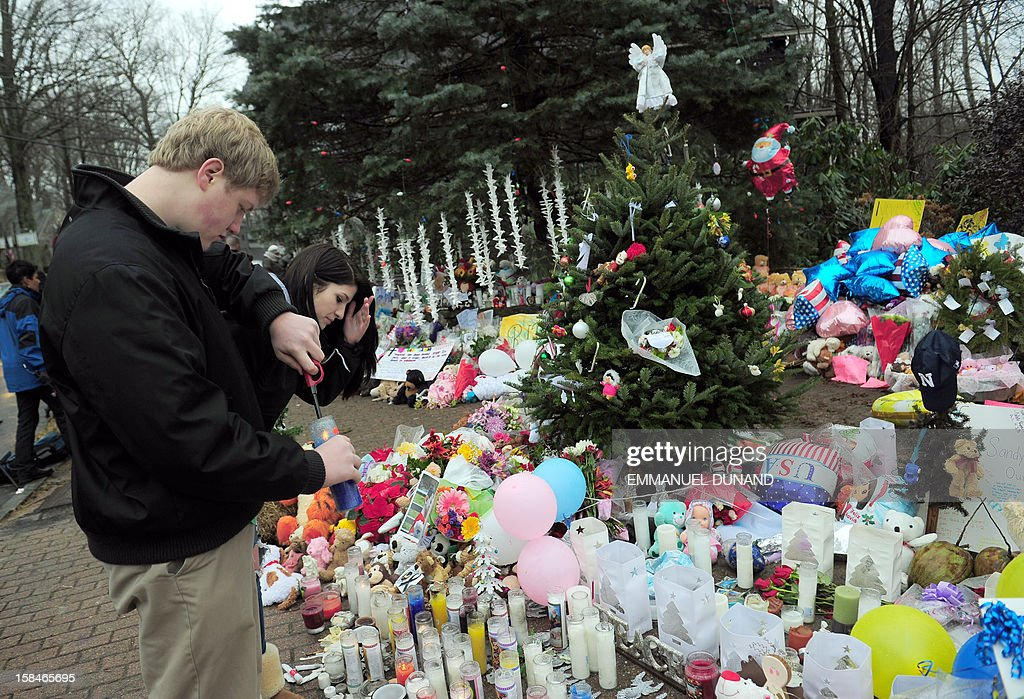 People pay their respects at a makeshift shrine to the victims of an elementary school shooting in Newtown, Connecticut, December 17, 2012. Funerals began Monday in the little Connecticut town of Newtown after the school massacre that took the lives of 20 small children and six staff, triggering new momentum for a change to America's gun culture. The first burials, held under raw, wet skies, were for two six-year-old boys who were among those shot in Sandy Hook Elementary School. On Tuesday, the first of the girls, also aged six, was due to be laid to rest. There were no Monday classes at all across Newtown, and the blood-soaked elementary school was to remain a closed crime scene indefinitely, authorities said.AFP PHOTO/Emmanuel DUNAND