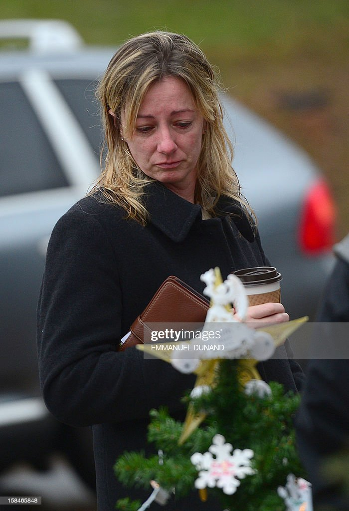 People pay their respects at a makeshift shrine to the victims of an elementary school shooting in Newtown, Connecticut, December 17, 2012. Funerals began Monday in the little Connecticut town of Newtown after the school massacre that took the lives of 20 small children and six staff, triggering new momentum for a change to America's gun culture. The first burials, held under raw, wet skies, were for two six-year-old boys who were among those shot in Sandy Hook Elementary School. On Tuesday, the first of the girls, also aged six, was due to be laid to rest. There were no Monday classes at all across Newtown, and the blood-soaked elementary school was to remain a closed crime scene indefinitely, authorities said. AFP PHOTO/Emmanuel DUNAND