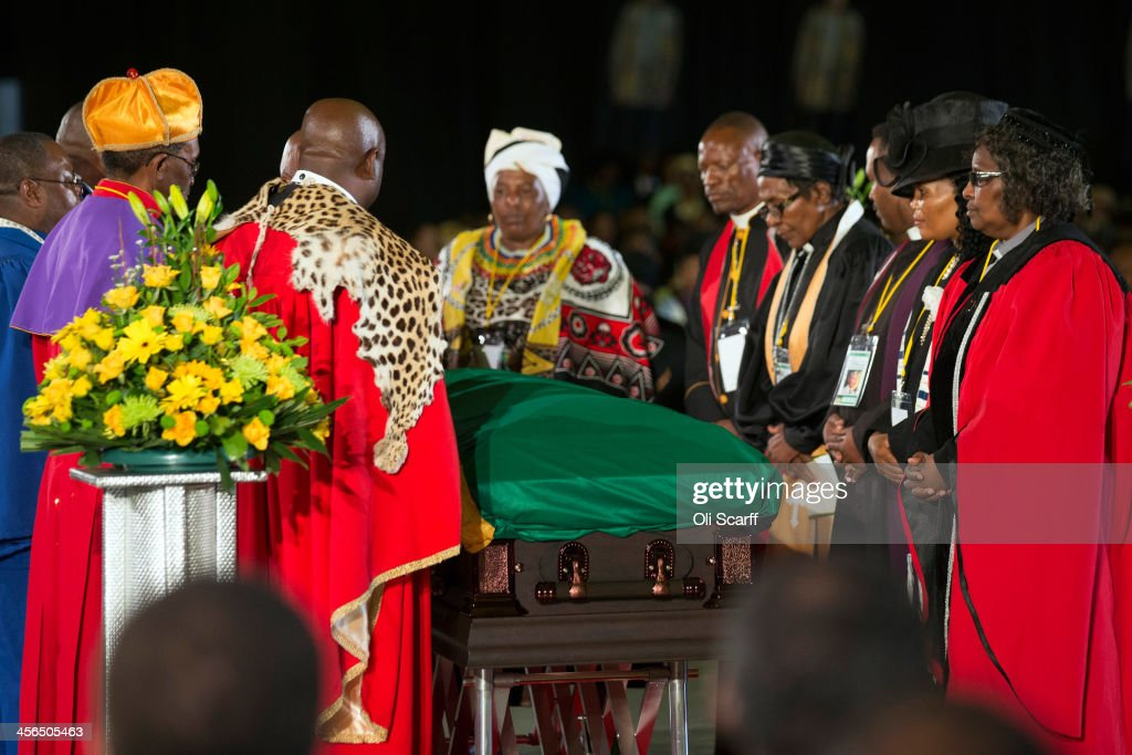 People pay their respects at an African National Congress (ANC) led alliance send off ceremony for former South African president Nelson Mandela takes place at Waterkloof military airbase on December 14, 2013 in Pretoria, South Africa. The ANC held an official send off ceremony as the body of former South African President prepares to make one final journey to his hometown of Qunu for burial. Mr. Mandela passed away on the evening of December 5, 2013 at his home in Houghton at the age of 95. Mandela became South Africa's first black president in 1994 after spending 27 years in jail for his activism against apartheid in a racially-divided South Africa.