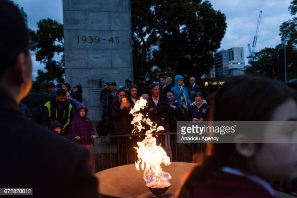 People pay their respects at the eternal flame during the dawn service of the ANZAC day commemoration at the Shrine of Remembrance in Melbourne...