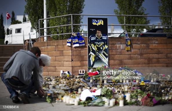 People pay their respects by laying flowers and candles outside the Swedish 'Kinnarps Arena' the HV71 ice hockey team home arena in the city of...