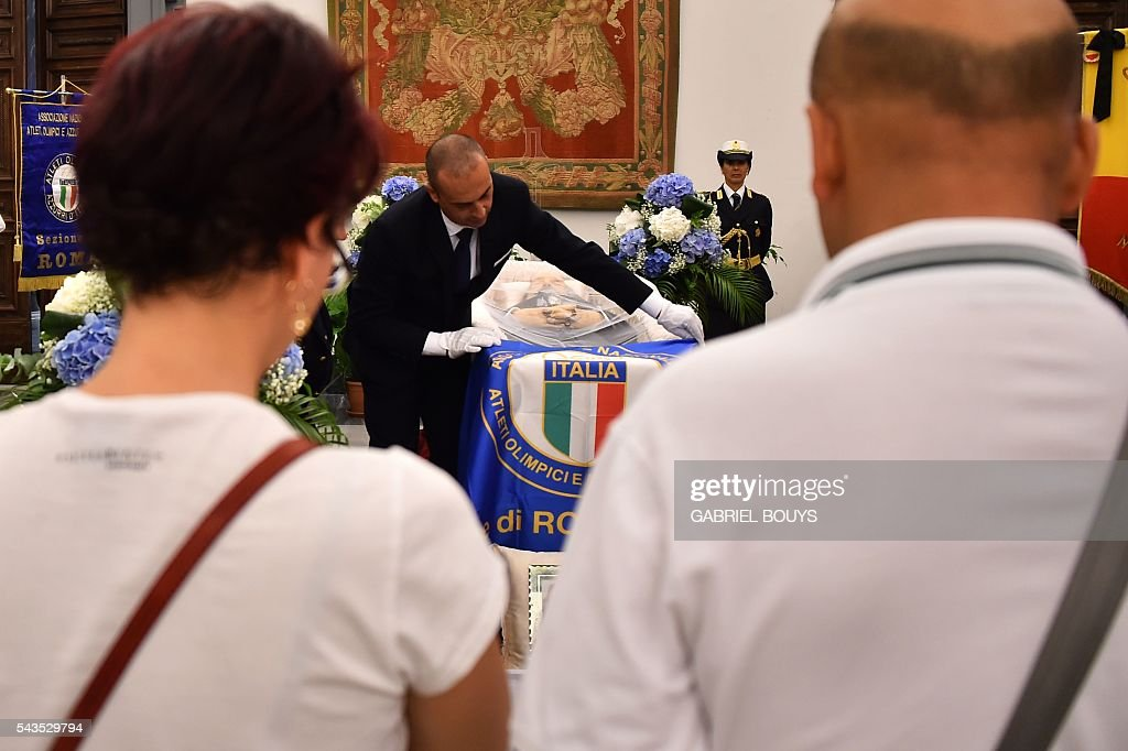 People pay their respects in front of the coffin of Italian actor Bud Spencer, lying in repose at Rome's city hall. Bud Spencer who starred in a string of spaghetti westerns, died on June 27 in Rome aged 86, his family confirmed. Spencer, born Carlo Pedersoli in Italy in 1929, played in 16 films alongside Terence Hill, whose real name was Mario Girotti. / AFP / GABRIEL