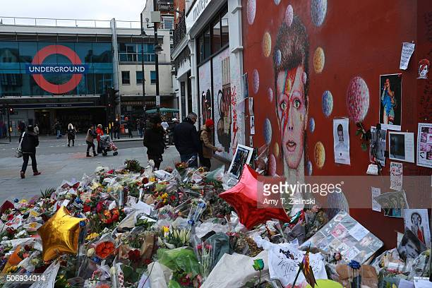 People pay their respects near the flowers letters and other items left on a mound continue to grow two weeks after the death of Brixton born English...