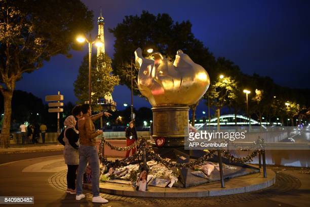 People pay their respects on August 30 2017 over the Alma bridge at the Flame of Liberty monument which became an unofficial memorial for Diana...