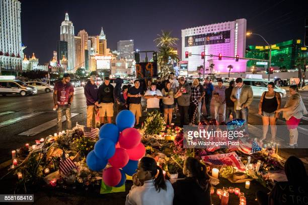 People pay tribute for Sunday's night mass shooting victims at vigil along Las Vegas Boulevard near Mandalay Bay hotel on Wednesday October 4 in Las...