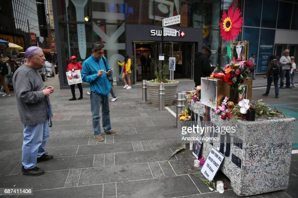 People pay tribute in front of s makeshift memorial that has been created in Times Square for Alyssa Elsman who died in a car accident last week in...