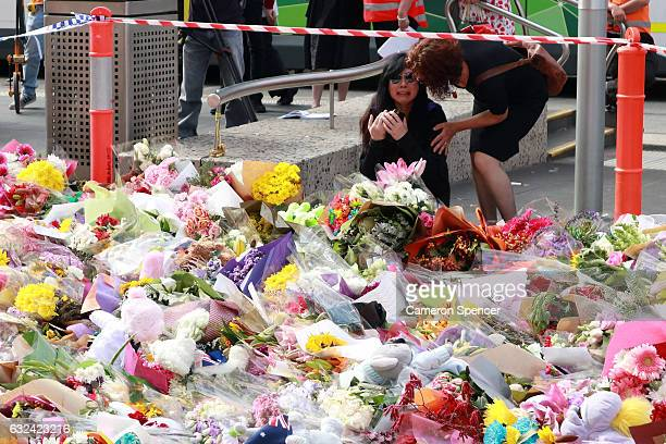 People pay tribute leaving flowers at a temporary memorial on Bourke Street Mall on January 23 2017 in Melbourne Australia Five people including an...