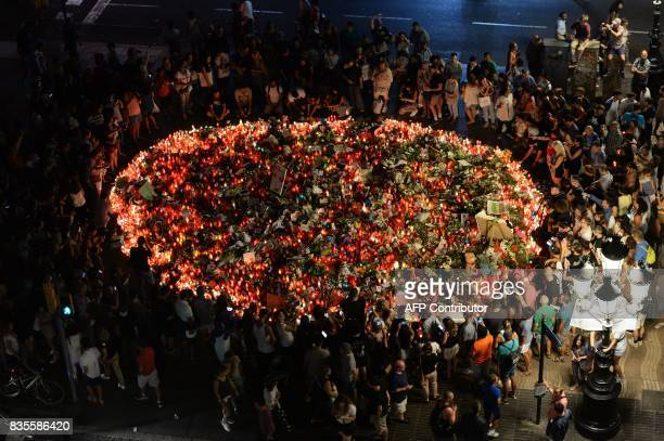 People pay tribute to the victims of the Barcelona attack on Las Ramblas boulevard in Barcelona on August 19 two days after a van ploughed into the...