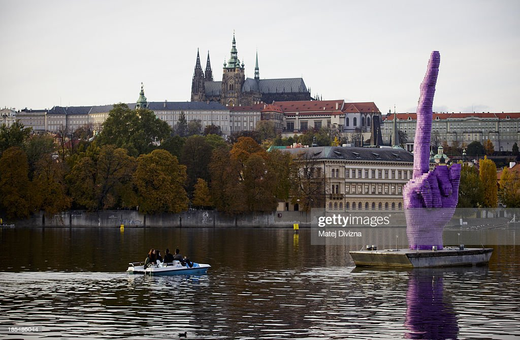 People pedal boat past the sculpture 'Middle Finger ' by David Cerny as it stands pointing towards Prague Castle, the seat of the Czech President Milos Zeman, on the Moldau river on October 21, 2013 in Prague, Czech Republic.