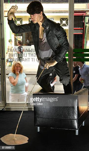 People peer in the window at a mannequin posed as a drunken man standing on a chair urinating on a carpet on June 17 2008 in London England The...