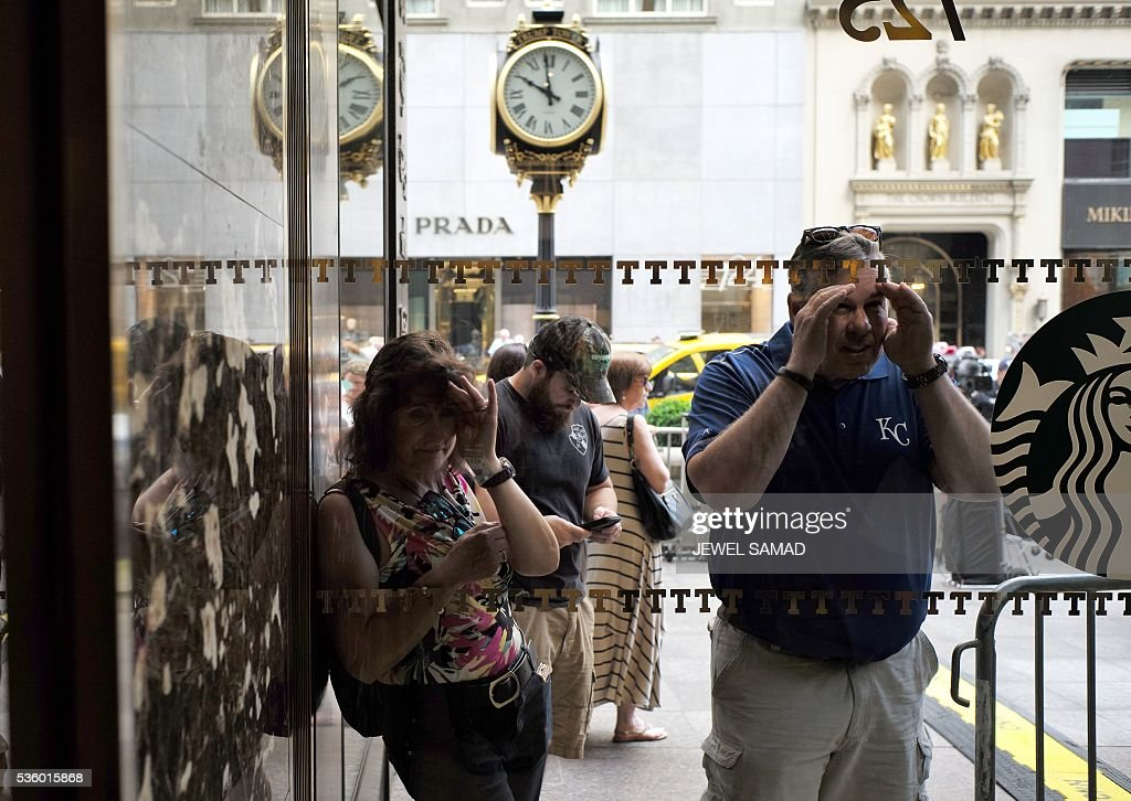 People peer through a glass window into the Trump Tower where US Republican presidential candidate Donald Trump will be holding a press conference on May 31, 2016 in New York. / AFP / Jewel SAMAD