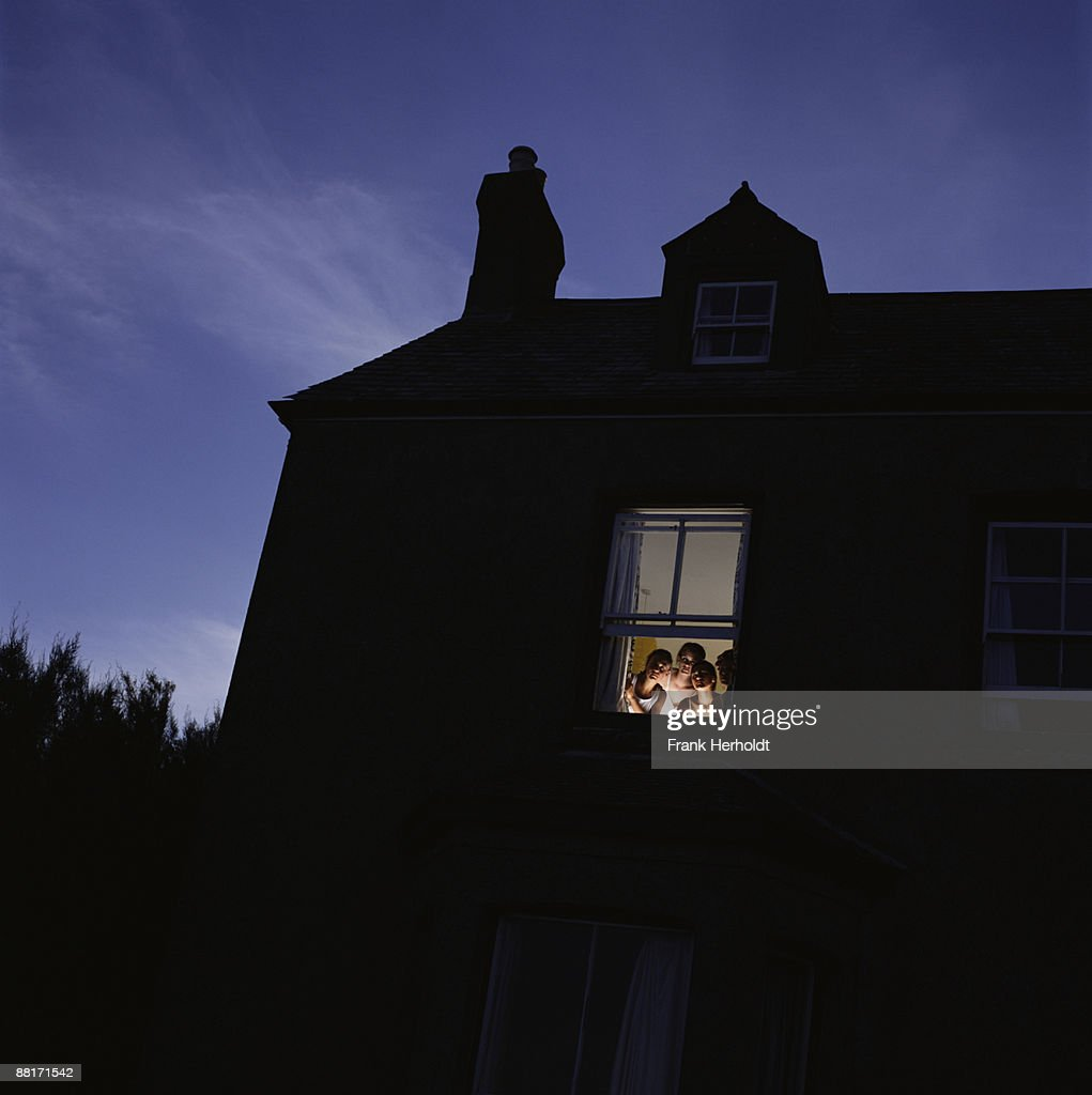 Open window at night - People Peering Out Open Window At Night Stock Photo