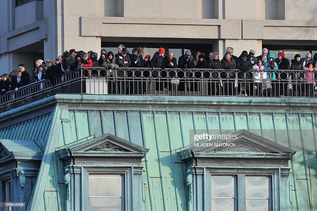 People perched from a balcony overlooking Pennsylvania Avenue watch as US President Barack Obama and First Lady Michelle Obama walk during the parade following Obama's second inauguration as the 44th US president on January 21, 2013 in Washington, DC. AFP PHOTO / Mladen ANTONOV