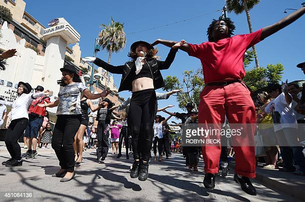 People perform a Michael Jackson Tribute flash mob dance on the 3rd Street Promenade in Santa Monica California ON June 22 2014 Fans of the King of...
