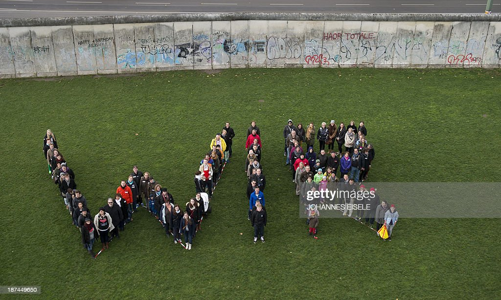 People perform a 'Wir' (we) next to the Berlin Wall memorial at Bernauer street on November 9, 2013 in Berlin on occasion of the 24th anniversary of the fall of the Wall. AFP PHOTO / JOHANNES EISELE