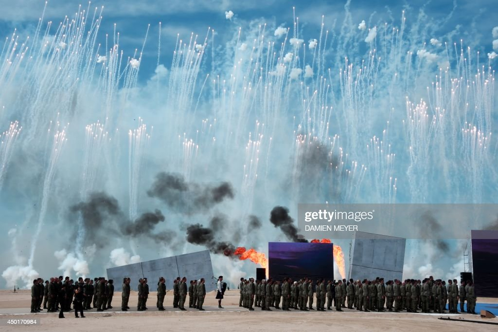 People perform as fireworks burst in the sky during the international D-Day commemoration ceremony on the beach of Ouistreham, Normandy, on June 6, 2014, marking the 70th anniversary of the World War II Allied landings in Normandy.