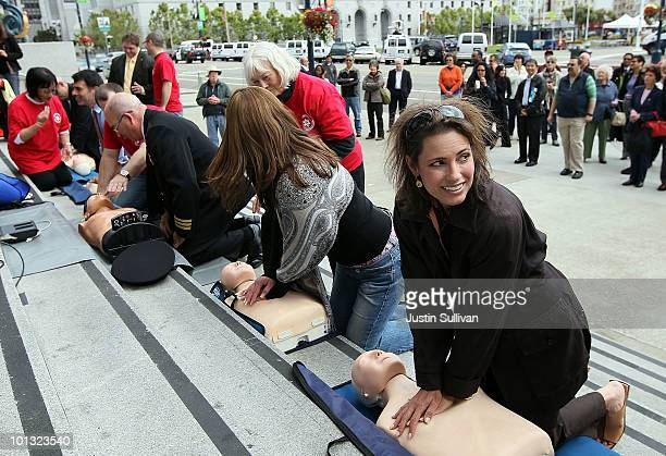 People perform chest compressions on mannequins while learning CPR on the steps of San Francisco city hall following a press conference celebrating...