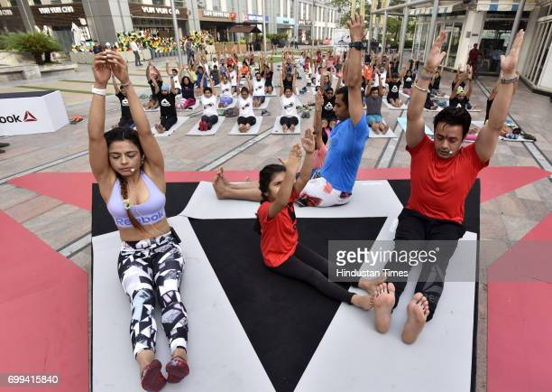 People perform different asanas during the International Yoga Day organized by Reebok and Ministry of AYUSH at Cyberhub on June 21 2017 in Gurgaon...