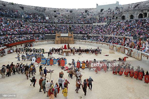 People perform in the Great Roman Games show 'The Triumph of Cesar' in the amphitheatre on May 5 2013 in Nimes southern France This event is a...