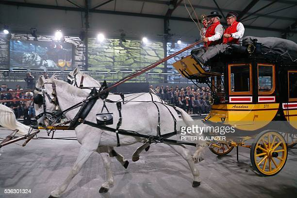 People perform on the old Gotthard diligence during the opening show directed by German director Volker Hesse on the opening day of the Gotthard rail...