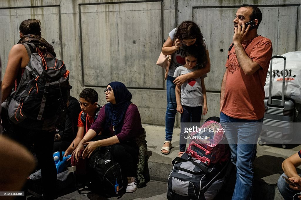 People phone and wait with their luggage outside the Ataturk airport in Istanbul, on June 28, 2016, after two explosions followed by gunfire hit the Turkey's biggest airport, killing at least 28 people and injured 20. All flights at Istanbul's Ataturk international airport were suspended on June 28, 2016 after a suicide attack left at least 10 people dead and 20 others wounded, Turkish television stations reported. / AFP / OZAN
