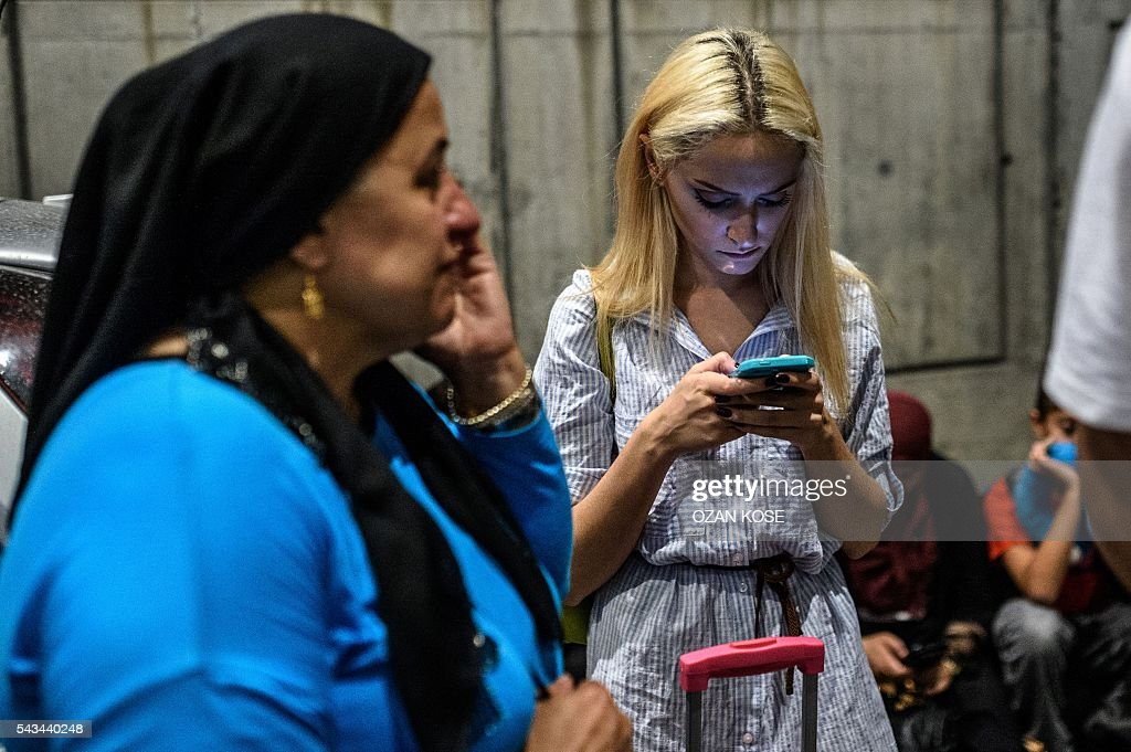 People phone outside as they leave the Ataturk airport in Istanbul, on June 28, 2016, after two explosions followed by gunfire hit the Turkey's biggest airport, killing at least 28 people and injured 20. All flights at Istanbul's Ataturk international airport were suspended on June 28, 2016 after a suicide attack left at least 10 people dead and 20 others wounded, Turkish television stations reported. / AFP / OZAN