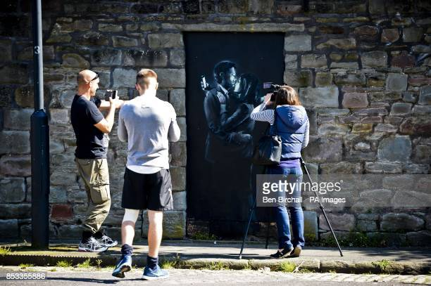 People photograph and film the latest officially confirmed Banksy artwork named Mobile Lovers featuring a man and a woman embraced and looking at...