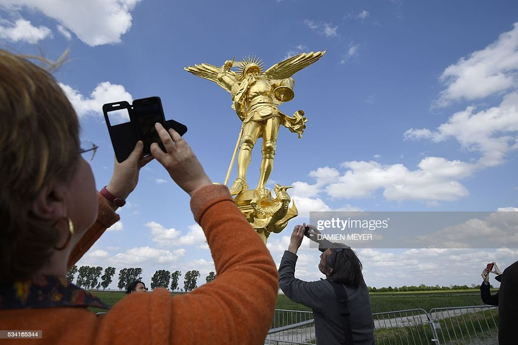 People photograph the statue of the Archangel Michael, regilded and restored with a new lighting rod, on the eve of its placement back atop the Mont Saint-Michel Abbey on May 25, 2016 in Mont Saint-Michel. / AFP / DAMIEN