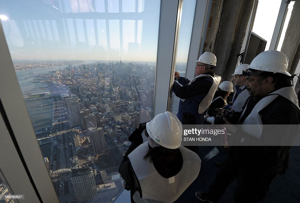 People photograph the view as officials from The Durst Organization, Legends Hospitality LLC and The Port Authority of New York & New Jersey give a preview to the news media of the One World Observatory site, the planned public observation deck under construction on the 100th floor of One World Trade Center April 2, 2013 in New York. AFP PHOTO/Stan HONDA