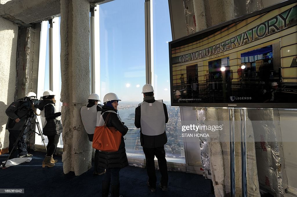 People photograph the view as officials from The Durst Organization, Legends Hospitality LLC and The Port Authority of New York & New Jersey give a preview to the news media of the One World Observatory site, the planned public observation deck under construction on the 100th floor of One World Trade Center April 2, 2013 in New York. An artists' version of the Observatory is seen on a video screen (R).AFP PHOTO/Stan HONDA