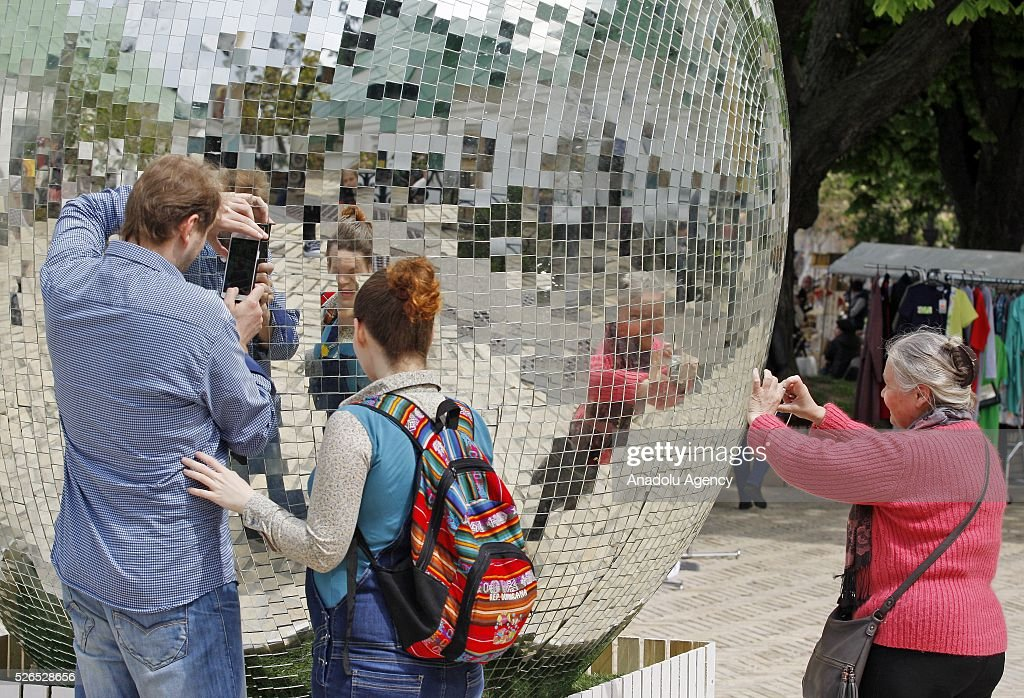People photographed a giant egg, named 'Diamond Easter Egg',3.5 m high, which is decorated with more than 15,000 mirror particles during the Ukrainian Easter hand made fair 'Easter country' at the Kiev-Pechersk Lavra in Kiev, Ukraine on April 30, 2016.