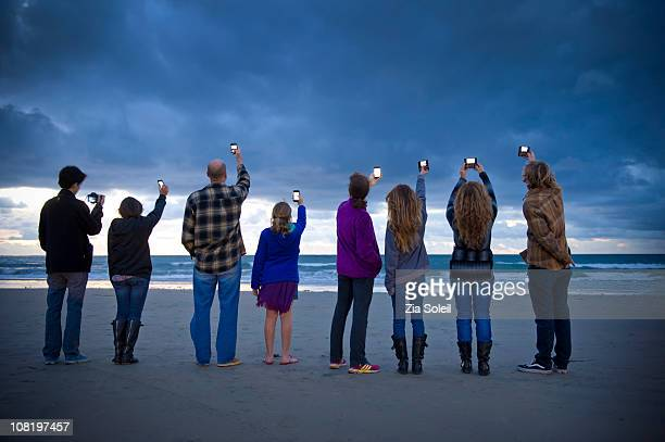 people photographing the sunset with smart phones