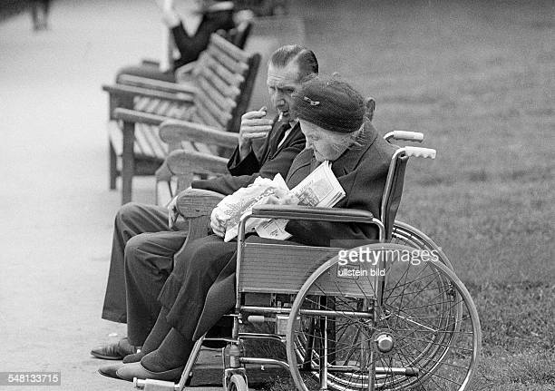 people physical handicap older woman sits in a wheelchair her husband sits beside her on a bench aged 65 to 75 years Great Britain England London