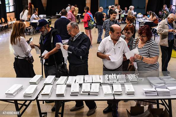 People pick up their ballot papers before casting it for municipal elections at a polling station on May 24 2015 in Barcelona Spain Spaniards are...