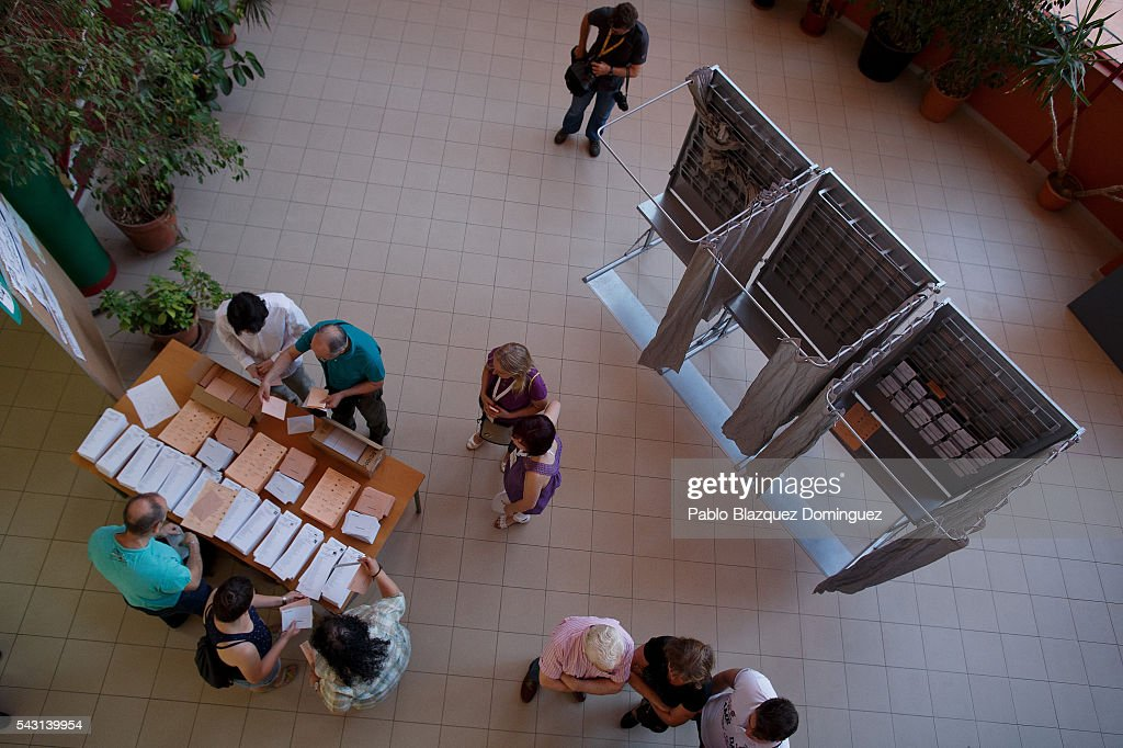 People pick up their ballots to vote at a polling station during the Spanish General Elections on June 26, 2016 in Madrid, Spain. Spanish voters head back to the polls after the last election in December failed to produce a government. Latest opinion polls suggest the Unidos Podemos left-wing alliance could make enough gains to come in second behind the ruling center right Popular Party.