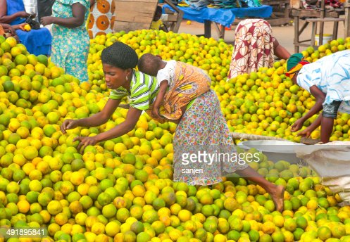 People picking oranges at the market in Ghana, Africa
