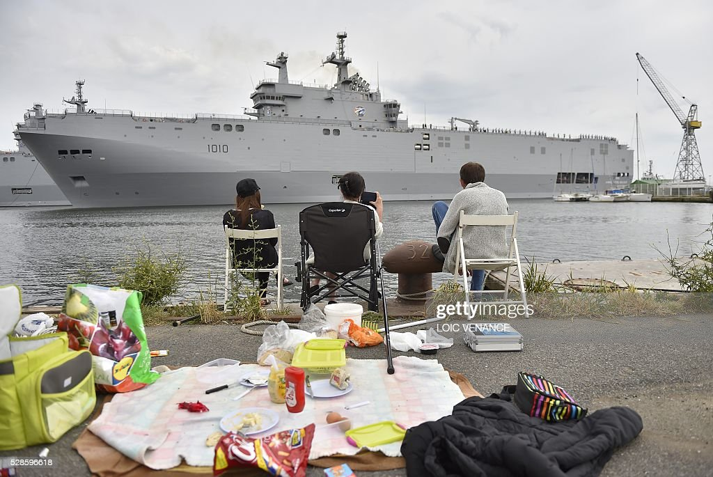 People picnic as the Gamal Abdl Nasser (ex-Vladivostok) Mistral class ship leaves the harbour for a one week training session on May 6, 2016 in Saint-Nazaire, western France. The 'Nasser', first one of the two Mistral class ships sold by France to Egypt after its first sale cancellation to Russia, leaves Saint-Nazaire (Loire-Atlantique) on Friday for a week of Egyptian crew training at sea. / AFP / LOIC