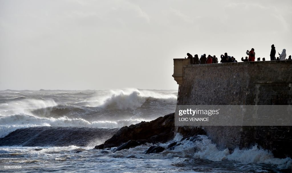 People picture the sea from a fortress in Les Sables-d'Olonne, western France, on February 9, 2016. High winds buffeted northwestern Europe on February 8, leaving one woman in France in a coma after she was hit by an advertising hoarding. Electricity was cut to 5,000 homes in northern France. / AFP / LOIC VENANCE