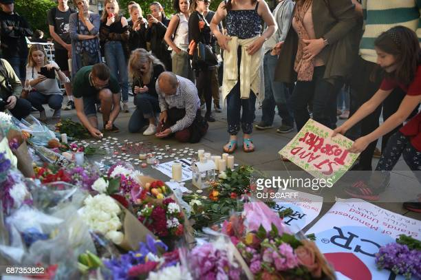 People pile up flowers and arrange candles and signs at a vigil in Albert Square in Manchester northwest England on May 23 in solidarity with those...