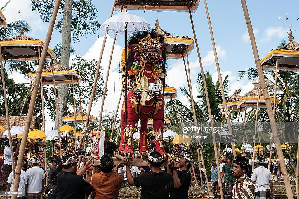 People place a sarcophagus into position at the cremation during a Balinese Hindu mass cremation on August 18, 2013 in Ubud, Bali, Indonesia. More than 60 corpses were collectively cremated to share the expense of the ceremony. Well known as Ngaben, it is one of the most important ceremonies for Balinese Hindu people, as they believe it will free the spirit from the deceased body so it can reincarnate.