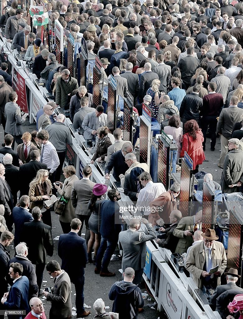 People place bets before a race on the final day of the Cheltenham Festival on March 14, 2014 in Cheltenham, England. Thousands of racing enthusiasts have been at the four-day festival, which ends today with the festival's Gold Cup and is seen as many as the highlight of the jump racing calendar.