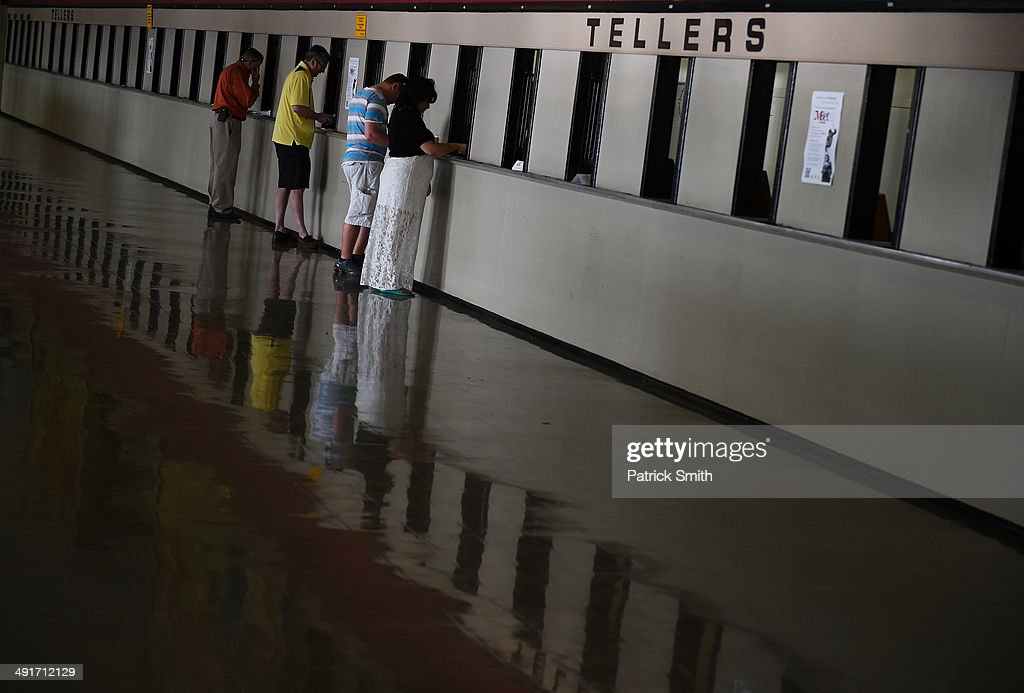 People place bets prior to the 139th running of the Preakness Stakes at Pimlico Race Course on May 17 2014 in Baltimore Maryland