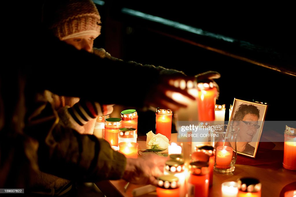 People place candles next to a picture of one of the three woman killed during a march on January, 5, 2013 in memory of the victims of a shooting in the village of Daillon. A gunman with psychiatric and drug problems killed three women and wounded two men on January 3, 2013 in a shooting spree in the tiny village where he lived in the mountains of southern Switzerland. Police shot and wounded the suspect after he threatened them with a gun following the attack in Daillon that raised fresh questions about the country's liberal gun ownership laws.