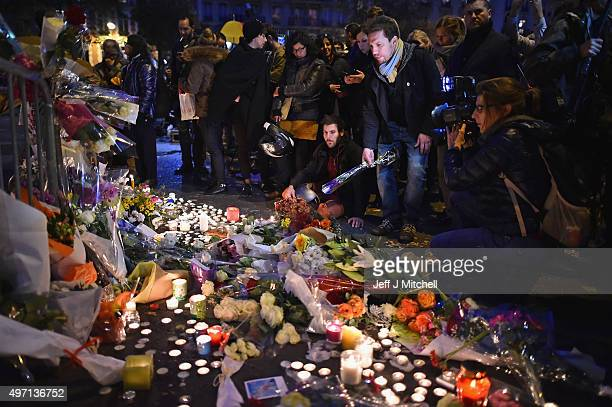 People place flowers and candles on the pavement near the scene of yesterday's Bataclan Theatre terrorist attack on November 14 2015 in Paris France...