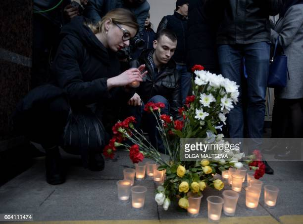 People place flowers and lit candles in memory of victims of the blast in the Saint Petersburg metro outside Sennaya Square station on April 3 2017...