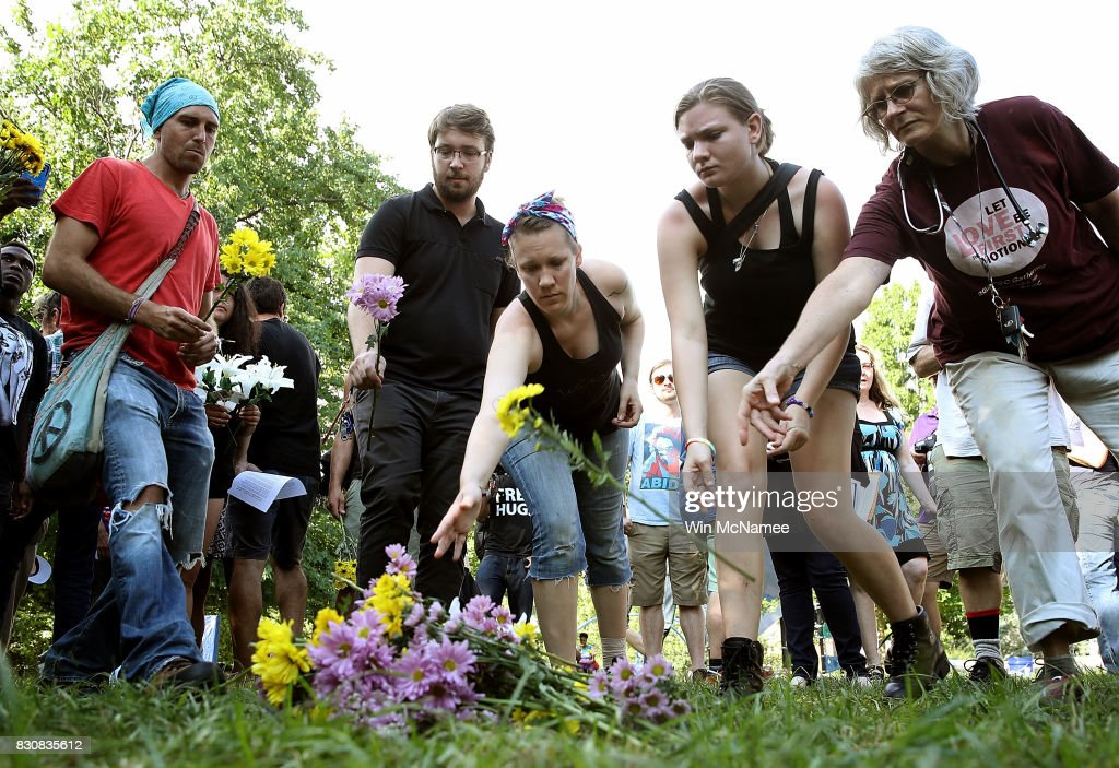People place flowers at a makeshift memorial during a vigil for those who were injured and died when a car plowed into a crowd of anti-facist counter-demonstrators marching near a downtown shopping area August 12, 2017 in Charlottesville, Virginia. The car allegedly plowed through a crowed, and at least one person has died from the incident, following the shutdown of the 'Unite the Right' rally by police after white nationalists, neo-Nazis and members of the 'alt-right' and counter-protesters clashed near Emancipation Park, where a statue of Confederate General Robert E. Lee is slated to be removed.