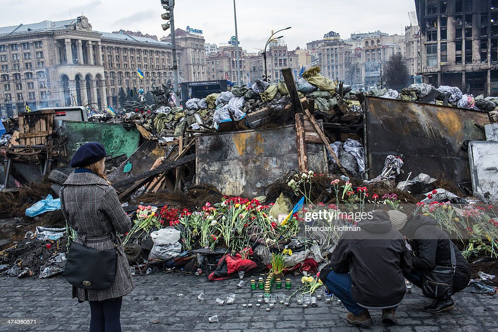 People place flowers at a memorial to anti-government protesters killed in chashes with police on Independence Square on February 23, 2014 in Kiev, Ukraine. After a chaotic and violent week, Viktor Yanukovych has been ousted as President as the Ukrainian parliament moves forward with scheduling new elections and establishing a caretaker government.