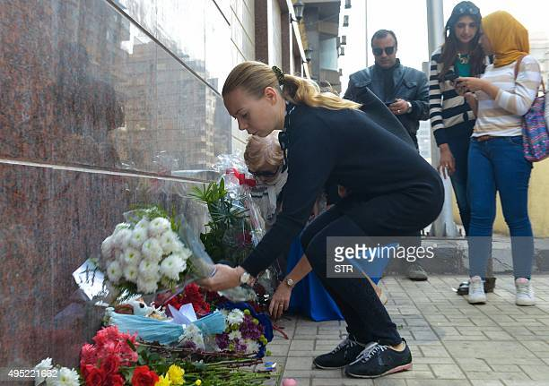 People place flowers in front of the Russian ambassy in Cairo to pay respect to the victims of a Russian airliner that crashed in Egypt's Sinai...