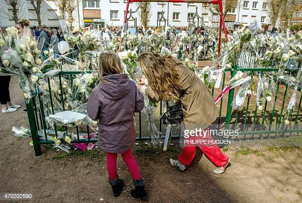 People place flowers on a playground gate as thousands of people pay their respect on April 18 2015 to nineyearoldgirl Chloe who was raped and killed...