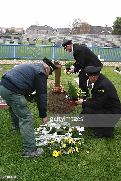 People place flowers on the grave of a four to fivedayold baby boy who was found 12 October 2007 washed up on a beach in Oostende 25 October 2007 in...